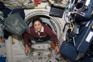 Space Living: Astro Home - Photo 21 of 32 - Astronaut Nicole Stott, STS-128 mission specialist, floats through a hatch on the Space Shuttle Discovery during flight day three activities. Photo taken August 30, 2009. Image courtesy of NASA.