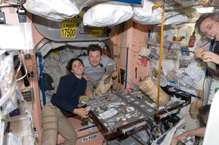 Space Living: Astro Home - Photo 22 of 32 - NASA astronaut Nicole Stott and Russian cosmonaut Roman Romanenko, both Expedition 20/21 flight engineers, are pictured at the galley in the Unity node of the ISS. Canadian Space Agency astronaut Robert Thirsk, Expedition 20/21 flight engineer, is mostly out of frame at right. Photo taken October 5, 2009. Image courtesy of NASA.