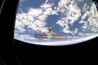 Space Living: Astro Home - Photo 30 of 32 - As seen through a window on Endeavour's aft flight deck, the ISS, then staffed with its fourth three-person crew, is contrasted against Earth's horizon during a farewell look from the shuttle following undocking. Photo taken December 15, 2001. Image courtesy of NASA.
