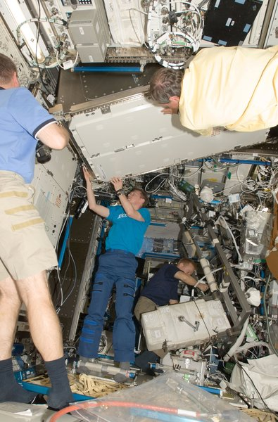 European Space Agency astronauts Christer Fuglesang (top foreground), STS-128 mission specialist; and Frank De Winne, Expedition 20 flight engineer, install a Materials Science Research Rack-1 (MSRR-1) in the Destiny laboratory of the ISS. NASA astronaut Kevin Ford (partially out of frame), STS-128 pilot; is at left; and NASA astronaut Tim Kopra, mission specialist, works in the background. Photo taken September 2, 2009. Image courtesy of NASA.