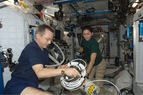 Canadian Space Agency astronaut Robert Thirsk and NASA astronaut Nicole Stott, both Expedition 21 flight engineers, work in the Harmony node of the International Space Station. Photo taken October 11, 2009. Image courtesy of NASA.