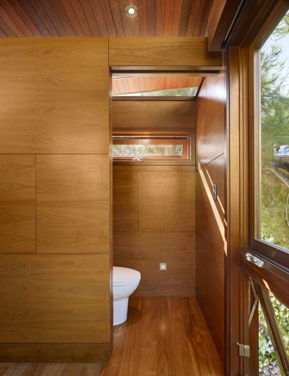 The treehouse serves also as temporary guest quarters, with modern-day amenities like a daybed, a sink, a toilet, a small refrigerator, a fireplace and a microwave. Tagged: Bath Room and Medium Hardwood Floor.  Photo 6 of 11 in An Atypical Tree House