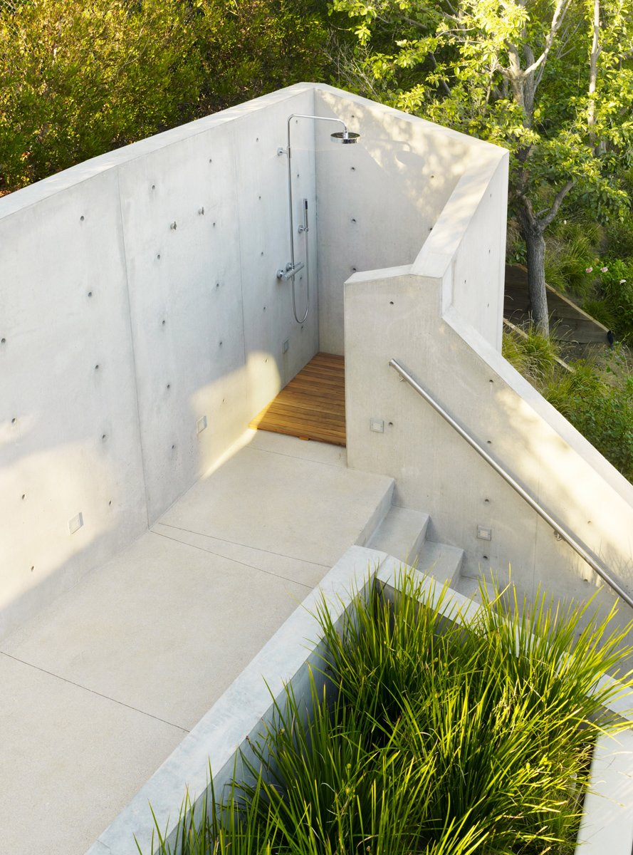 The outdoor shower below the treehouse was shaped and formed from concrete to be a truly private experience.  Photo 7 of 14 in These 13 Outdoor Showers Will Make You Consider One For Your Own Yard from An Atypical Tree House