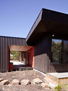 30 All-Black Exterior Modern Homes - Photo 13 of 30 - Courtyard House, Location: Somers Victoria Australia, Architect: Rowan Opat .Evolving from the notion of a series of outbuildings on a greenfi eld site, principles of passive solar design have informed this courtyard house. The northern eaves respond directly to shading becoming shallower in proportion to the depth of space as experienced in the square plan. As the dominant designed area, on this hectare site, the courtyard both surrounds and is surrounded by the house, creating a contained space within an otherwise semi-rural block.