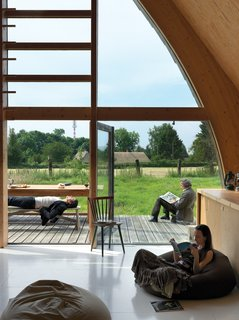 Modern Wooden A-Frame Retreat in France - Photo 4 of 11 - Like the barns Barache scampered through as a child, the house divides its length between loftlike open spaces like the living room, which opens onto a small deck perfect for open-air lolling, and stacked-box nooks and crannies.