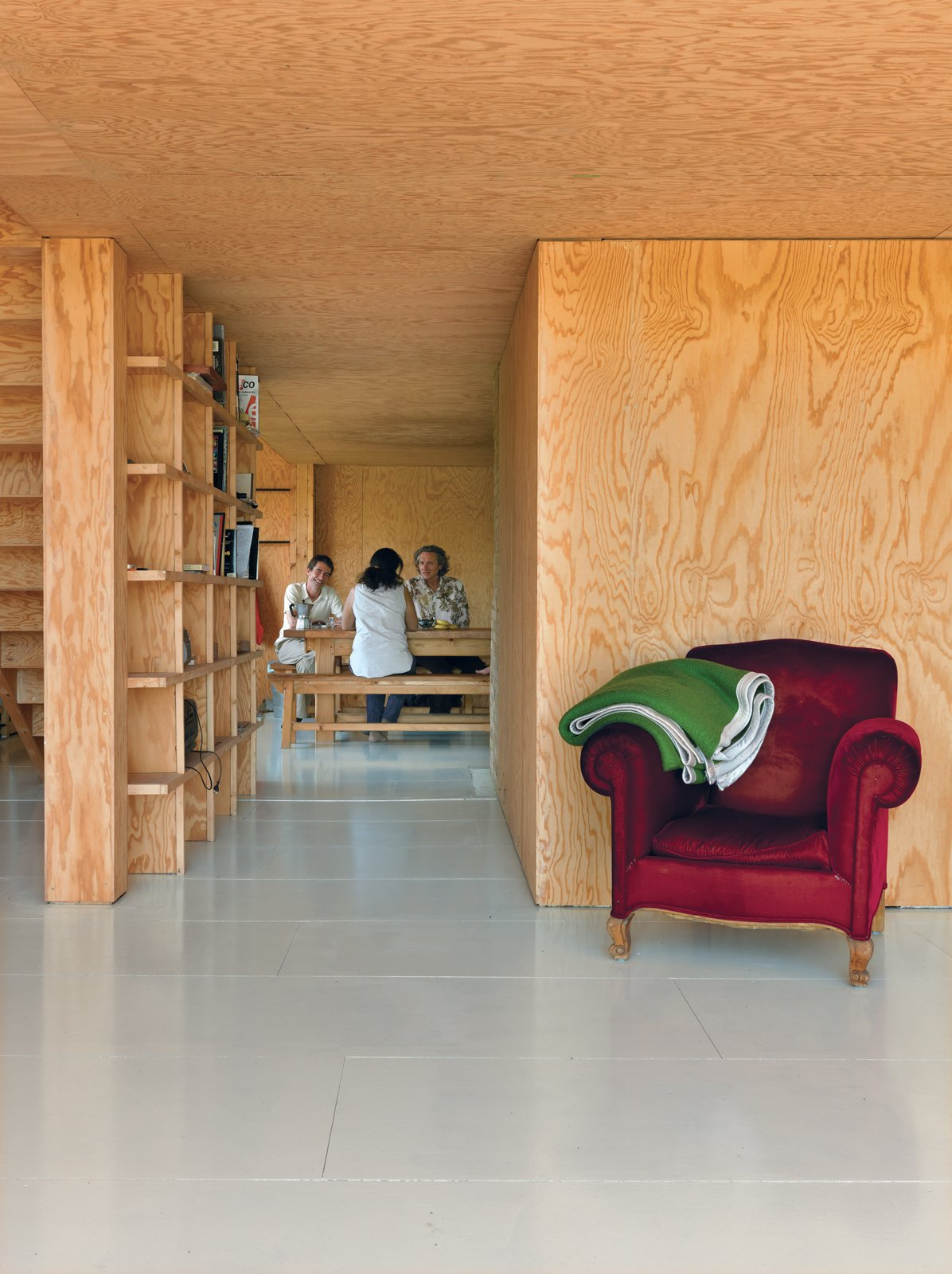 Cubic bookshelves do double duty as a dividing wall and as a sliding door. Tagged: Living Room and Chair.  Photo 6 of 11 in Modern Wooden A-Frame Retreat in France
