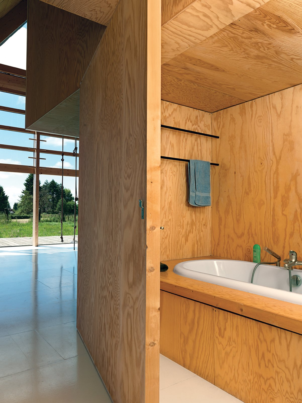 Cubic bookshelves do double duty as a dividing wall and as a sliding door opening up to a hidden bath.  Photo 3 of 11 in Modern Wooden A-Frame Retreat in France
