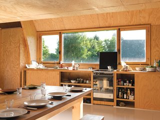 "In his kitchen built on the cheap, Barache installed appliances donated by a few architectural Good Samaritans. ""I don't even remember where the sink is from,"" he says. Two built-in sliding-door cabinets house the kitchen basics, and the custom-built dining set, a modern riff on the farmers' table and benches, is large enough to welcome family and visitors dropping in for a meal."