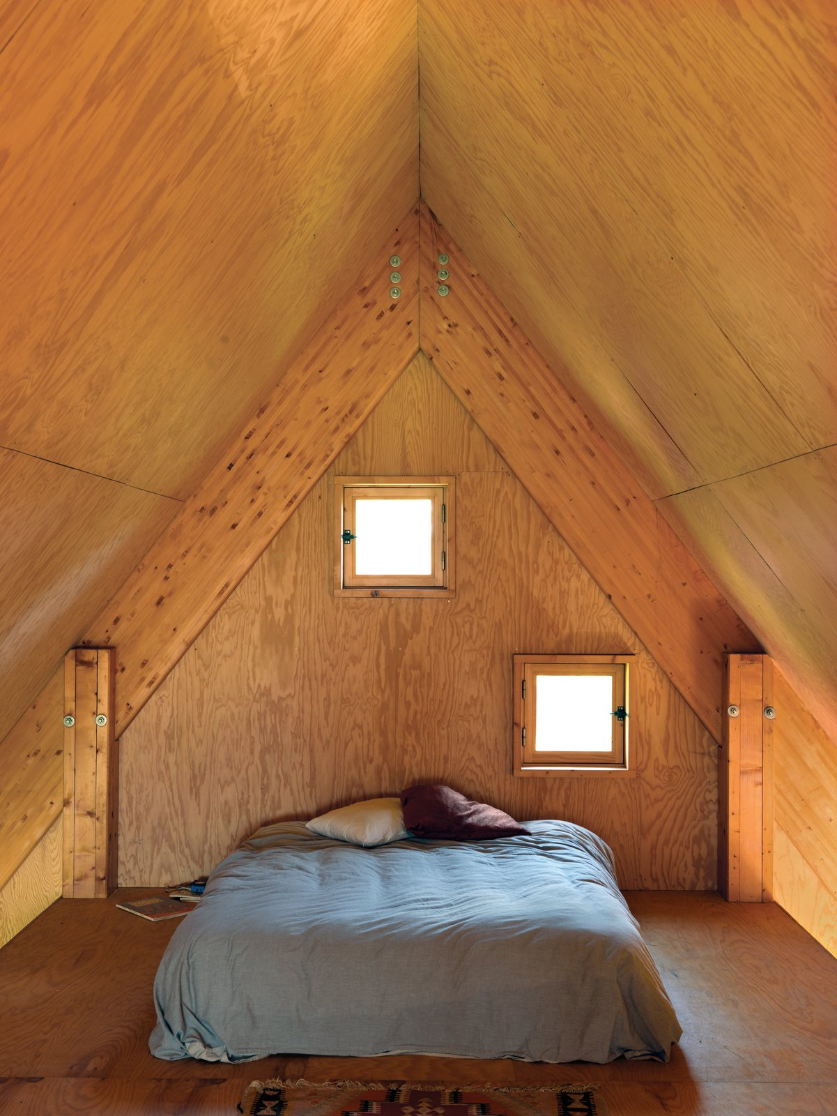 In the third-floor bedroom, peekaboo windows offer a glimpse of the surrounding fields. Tagged: Bedroom and Bed.  Photo 5 of 11 in Modern Wooden A-Frame Retreat in France
