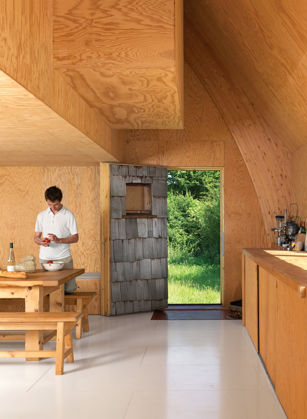 The exposed-wood motif continues inside, where plywood walls, as well as Barache and his guests, keep things warm. Tagged: Kitchen and Wood Cabinet.  Kitchen by Lara Deam from Modern Wooden A-Frame Retreat in France