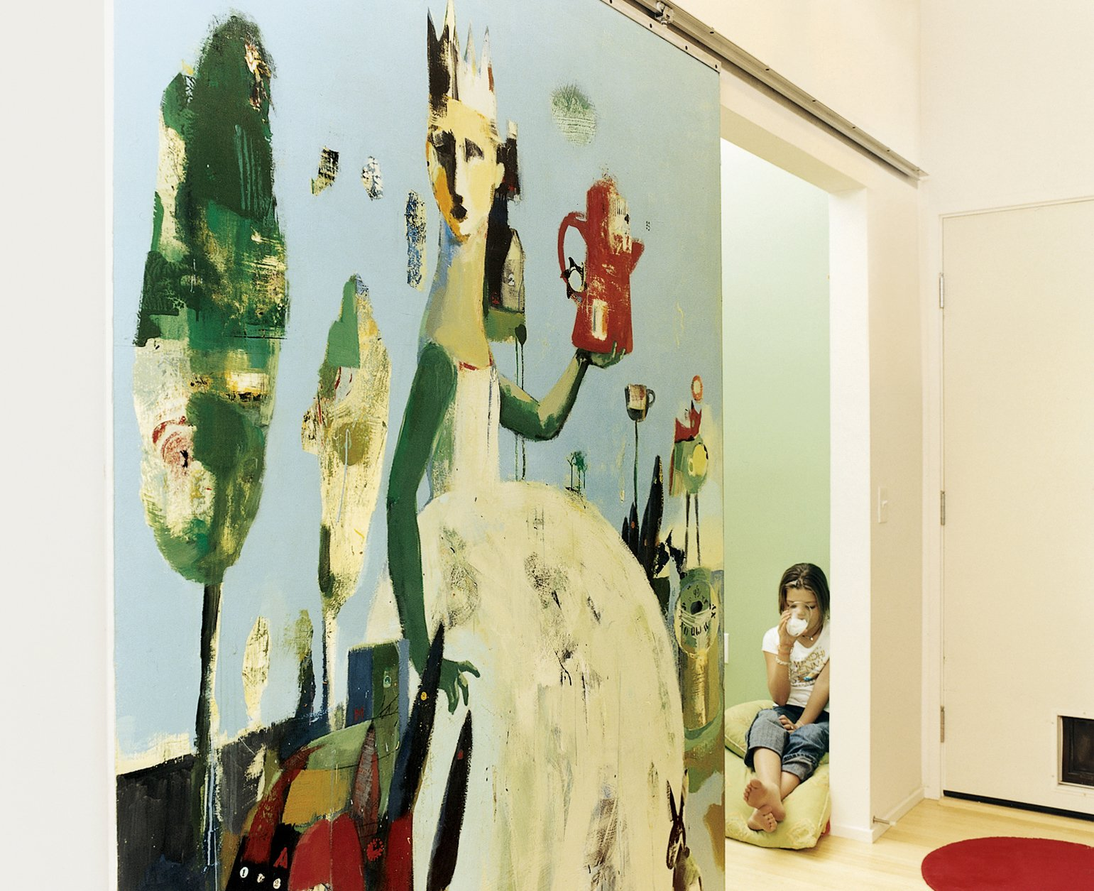 "The Lees commissioned local artist Blair Thornley to create a large painting, which Public then mounted on a slider. The painting now functions as a sliding door to close off the TV room when necessary. ""Blair coated it in acrylic,"" architect James Gates explains, ""so they don't have to worry about handprints.""  Photo 6 of 7 in The Family Tree"