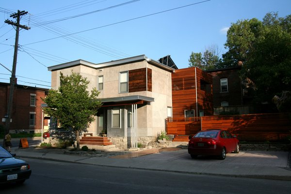The home's entrance is located just around the corner from the confectionary entrance. The bay window form is original, but was modernized with a concrete exterior. At right, housed in mostly reclaimed cedar, is the portion containing the upstairs deck. A new fence encloses the small, previously exposed yard.