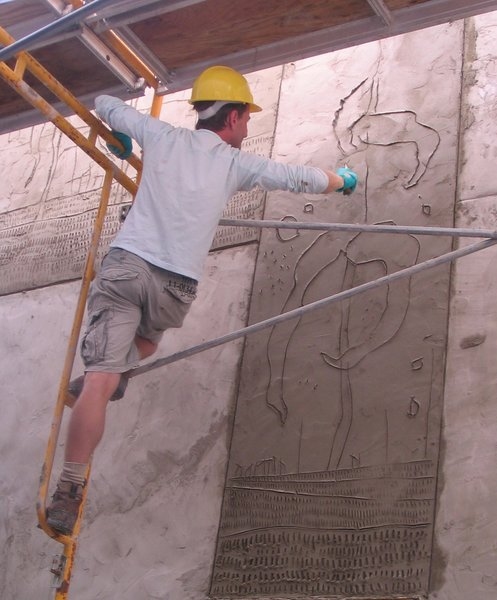 Griffin carves an exterior panel using a casuary bird femur bone knife—a dedication to early artistic tools and methods. Each panel received a fresh topcoat of concrete, after which the artist had no more than 15 minutes to make his marks before his canvas completely hardened.