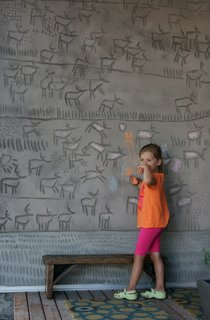 "The couple's daughter, Kalyna, puts her own spin on her father's engravings, which he calls a ""concrete coloring book."" Dedicating this side of the building to the earth, he carved herds of caribou into the panels. The abstract marks at the base skirt the entire exterior and were added for a consistent design element."