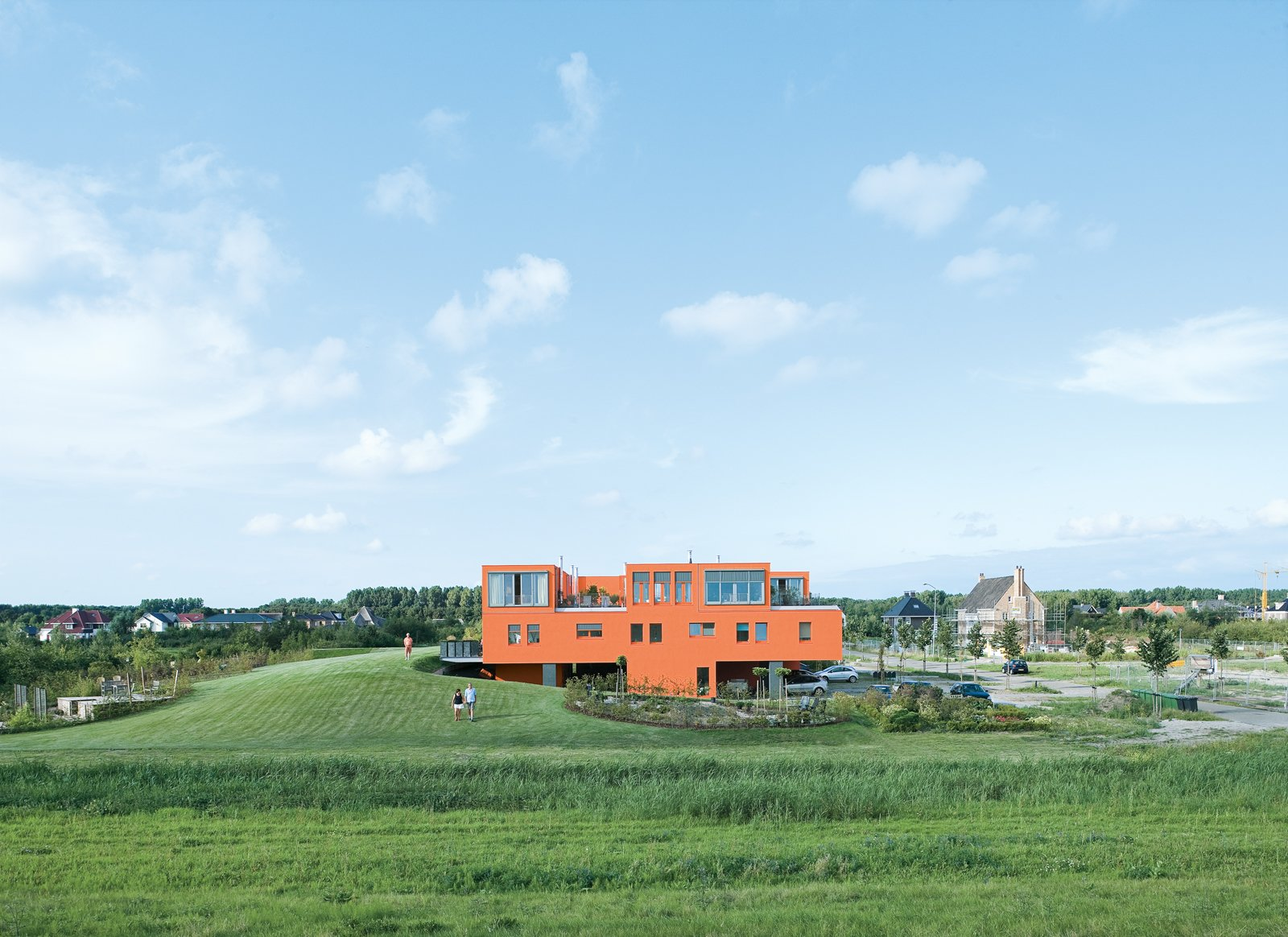 Seen here from the south, Villa van Vijven's orange facade is meant to mimic the tiled rooftops of Holland's country buildings, while the building's horizontal pull echoes the flat landscape. The second-floor living rooms look out on the 4,200-square-foot communal garden, one of only two shared spaces in the whole community. Bob Krone, Koos Sweringa, and Marianne Schram stroll the grounds.