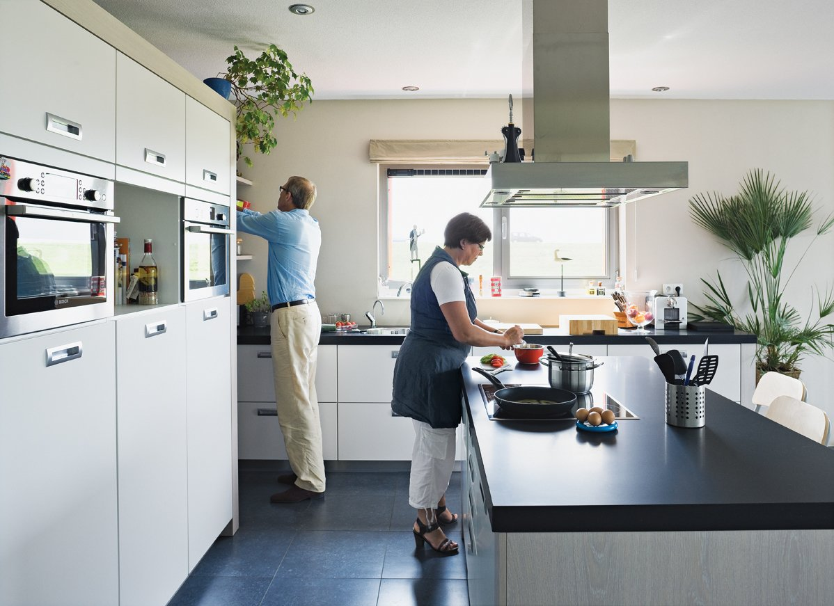 Koos Sweringa and Marianne Schram putter in the kitchen. Tagged: Kitchen, Range Hood, Cooktops, Wall Oven, Microwave, White Cabinet, and Wood Cabinet.  Photo 11 of 22 in Modern Communal Living in the Netherlands