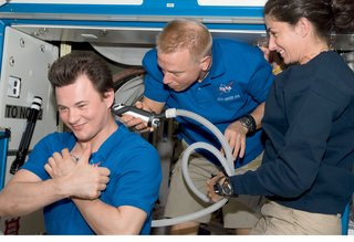 Space Living: Astro Home - Photo 2 of 32 - A haircut, performed by Tim Kopra for Roman Romanesko, calls for clippers connected to a vacuum to entrap cut hair. Image courtesy of NASA.