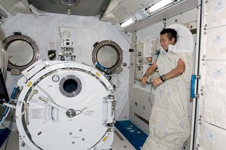 Space Living: Astro Home - Photo 13 of 32 - The ground-control crew sets all the schedules, including when to eat and sleep, since the day's 16 sunsets quickly become disorienting. In the ISS's Kibo laboratory, Koichi Wakata sleeps while secured to the wall in a sleeping bag. Image courtesy of NASA.