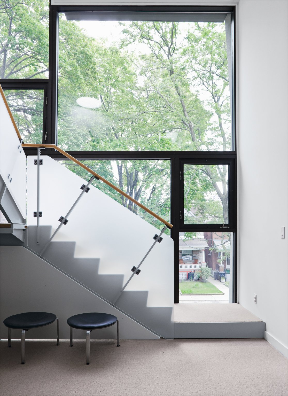 The second-floor family room is fronted by an L-shaped staircase with an opaque guardrail that provides some privacy for the front facade.  190+ Best Modern Staircase Ideas by Dwell from Narrow Modernist Three-Story Home in Toronto