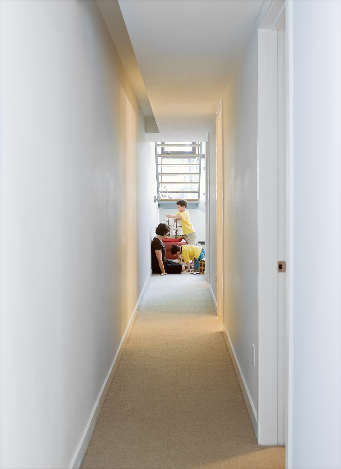 Down the corridor from the boys' bedrooms is the family room. Tagged: Hallway and Carpet Floor.  Photo 7 of 18 in Narrow Modernist Three-Story Home in Toronto