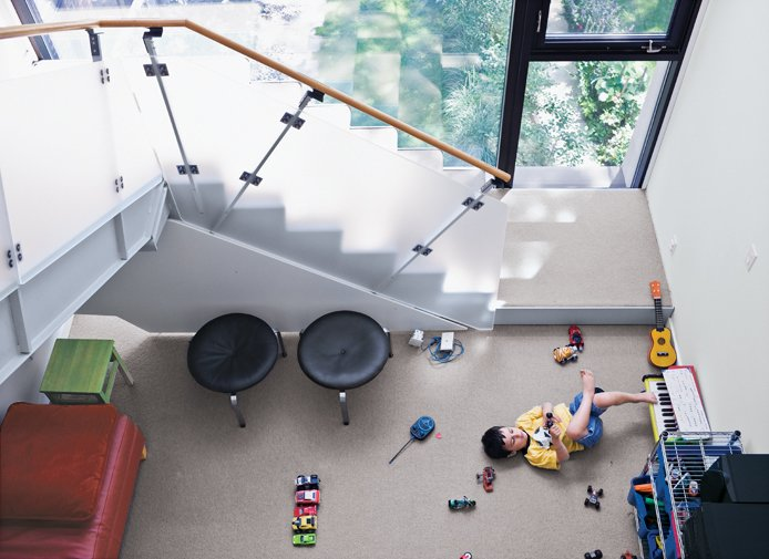 The kids play in the family room just beneath the stairs. Tagged: Kids Room, Family Room, Carpet Floor, and Chair.  Photo 8 of 18 in Narrow Modernist Three-Story Home in Toronto