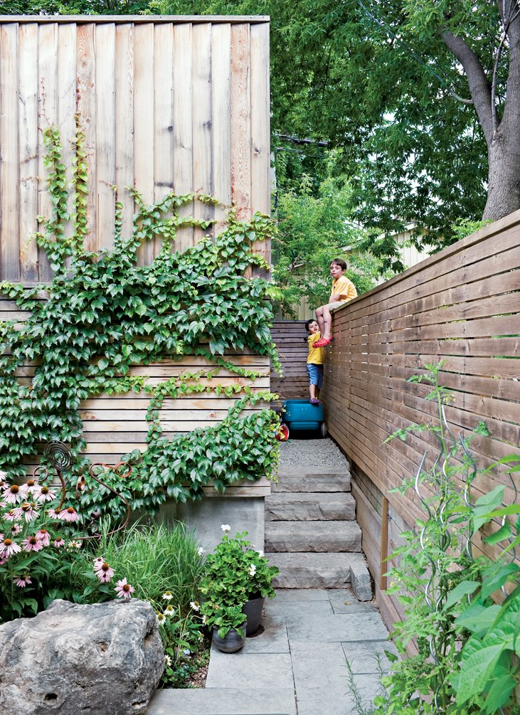 In the back, ivy climbs across the garage's raw cedar cladding next to a gate that allows access to the laneway—but the boys prefer to climb the fence.  Photo 9 of 18 in Narrow Modernist Three-Story Home in Toronto