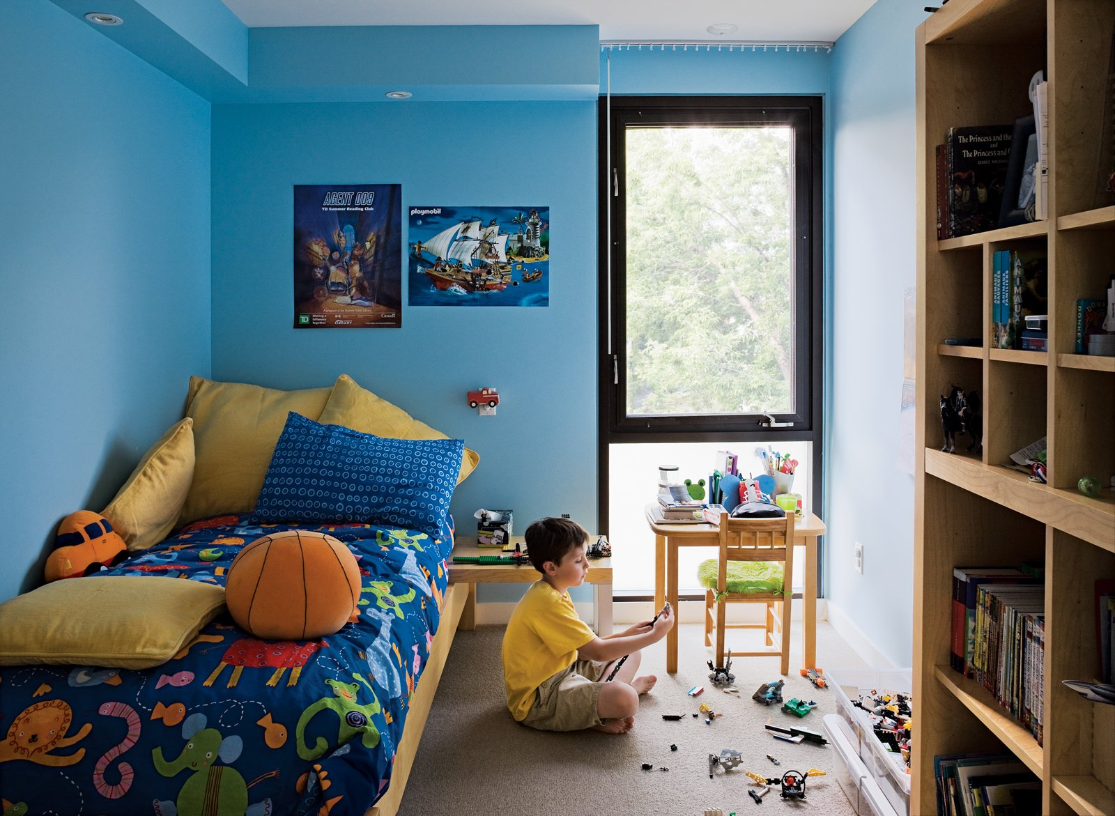 Griffin's room, which is exactly the same size as his brother's, gets good light from the backyard. Tagged: Kids Room, Bedroom, Boy Gender, Pre-Teen Age, Desk, Bed, Night Stands, Chair, Carpet Floor, Shelves, and Storage.  Photo 14 of 18 in Narrow Modernist Three-Story Home in Toronto