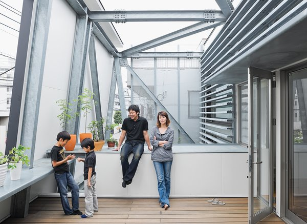 Slotted between the street-side enclosure and the living area is a breezy second-floor terrace. Brise soleil slats shade the interior. Yatabe's steel fabrication company created the robust, trusslike armature that extends from the house to support the deck and facade.