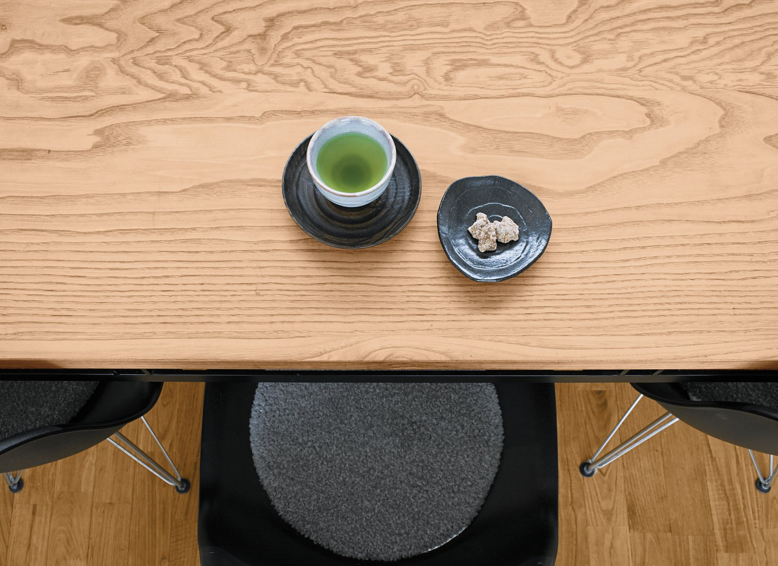 Green tea and a sweet for a guest. Tagged: Dining Room, Table, Chair, and Medium Hardwood Floor.  Green by Allie Miller from Small Box Home with Black Metal Facade in Japan