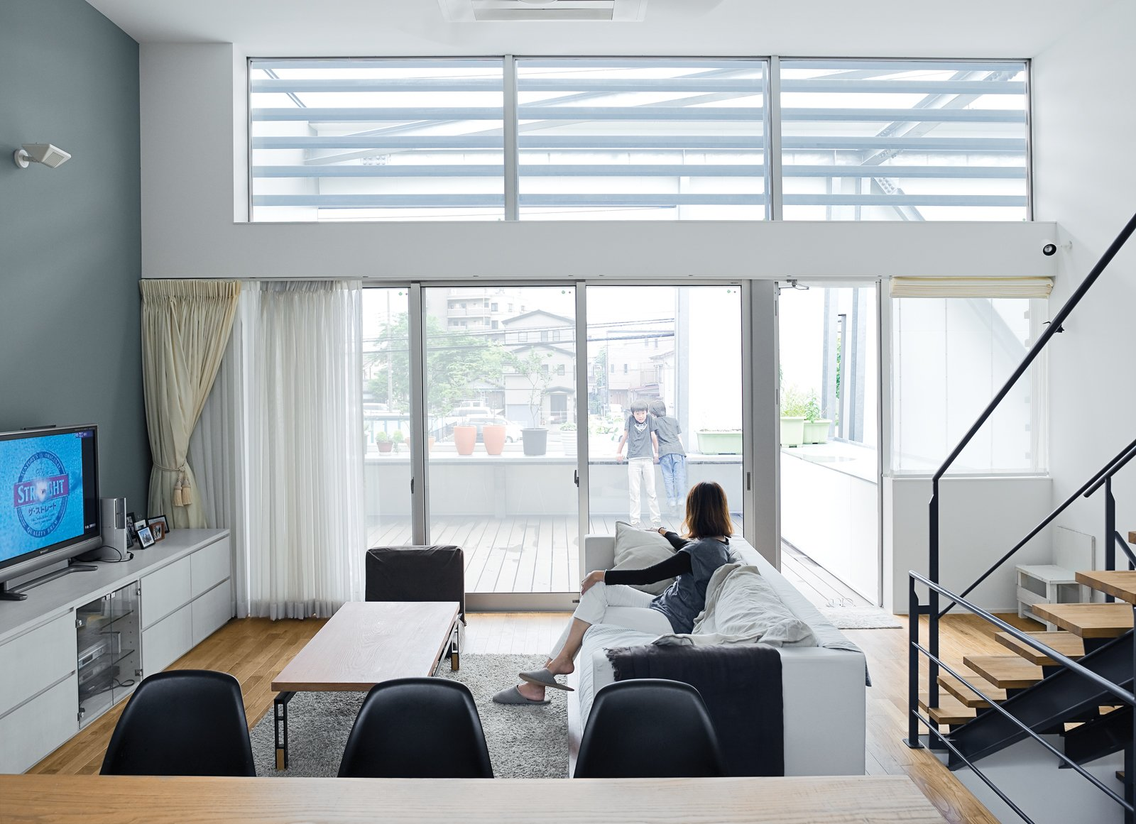 The family's hub is a high-ceilinged main room on the second level. It's open and casual and gets lovely morning light. Small Box Home with Black Metal Facade in Japan - Photo 6 of 14