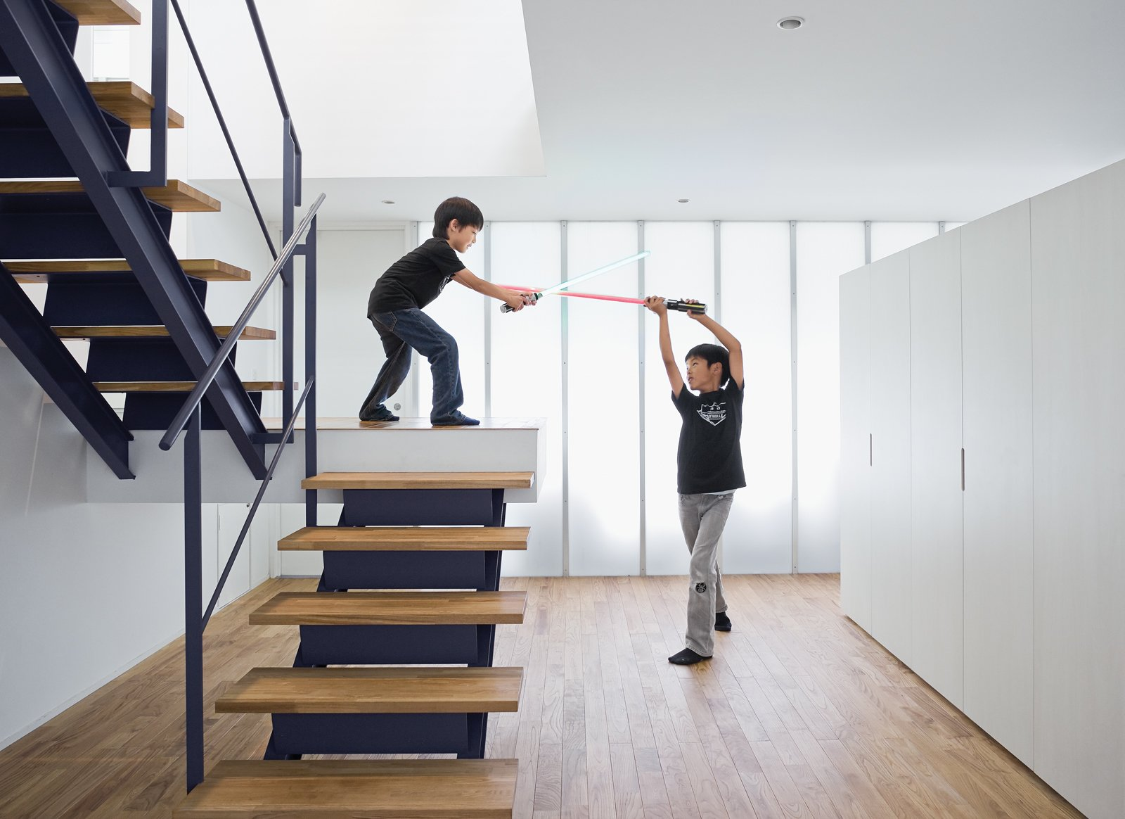 The open-tread stair leading from the garage to the second-floor living room sets the stage for a Star Wars–style duel. Tagged: Staircase, Metal Railing, and Wood Tread.  Photo 12 of 14 in Small Box Home with Black Metal Facade in Japan