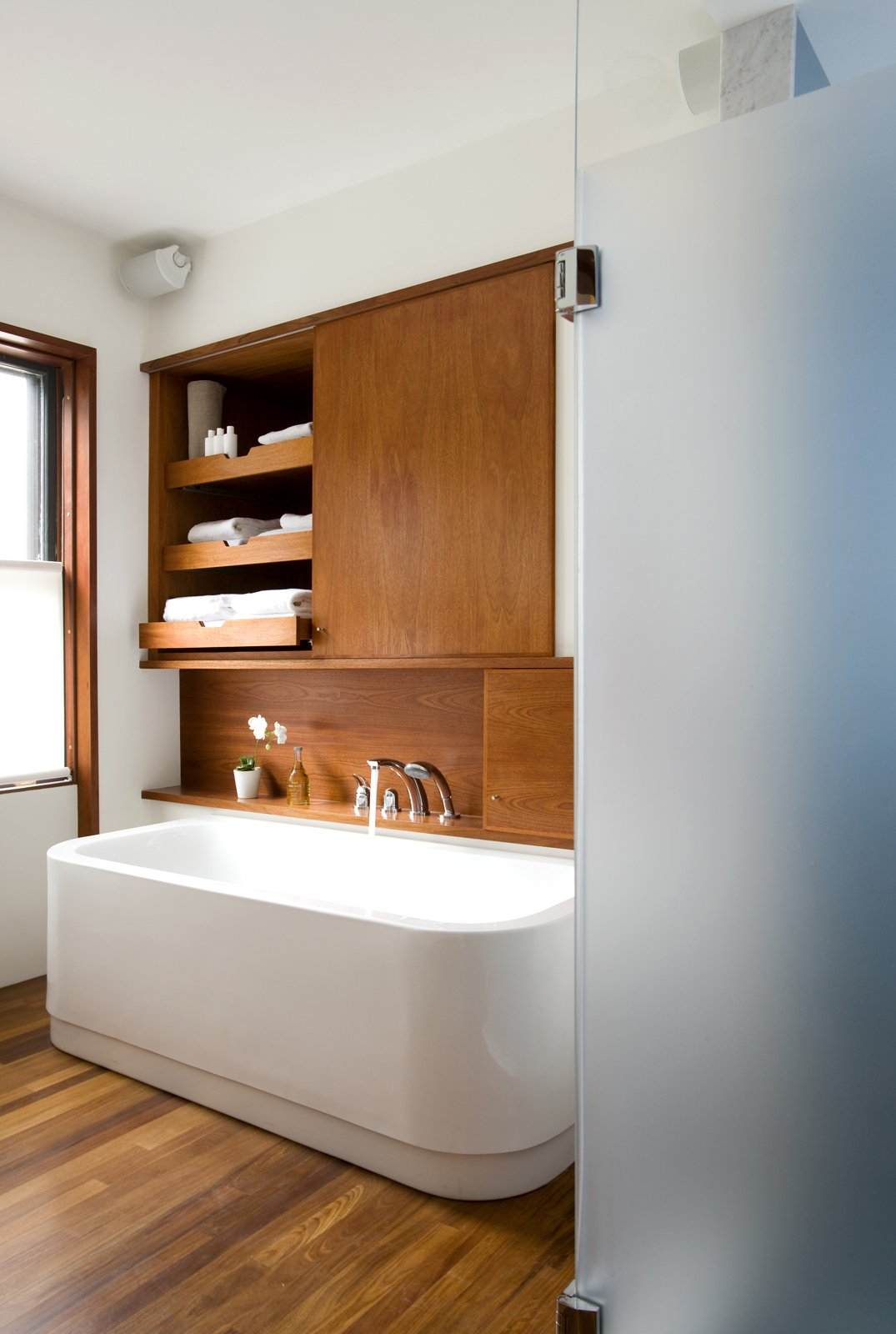 The leftmost cabinet above the Duravit bathtub (equipped with KWC fixtures) occupies the space where a doorway once lead into the living room, creating unnecessary traffic from the home's public spaces through to the master bedroom. The new bathroom features a minimal palette of white and teak.