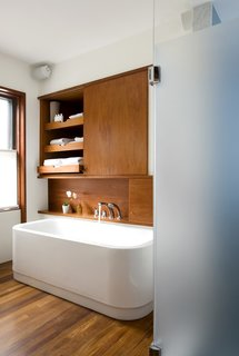 "The leftmost cabinet above the Duravit bathtub (equipped with KWC fixtures) occupies the space where a doorway once lead into the living room, creating unnecessary traffic from the home's public spaces through to the master bedroom.The new bathroom features a minimal palette of white and teak. ""It's able to hold up on boat decks so is good for a bathroom,"" Klug says. It also makes the heated floor that much nicer to walk on in the morning.<br><br>Photo by <br><br>Eric Roth"