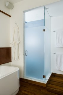 The shower is one corner of the renovated bathroom and adds a slash of color—a blue to match the color of the Aegean Sea as the homeowner remembered it after a trip to the Mediterranean.Butz and Klug chose towels bars and accessories from <br><br>Dornbracht to finish the room's look.Photo by <br><br>Eric Roth