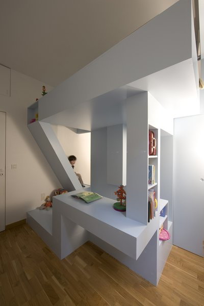 The bed seems to soar above the playing space, held up by bookshelf columns and a carefully angled staircase.
