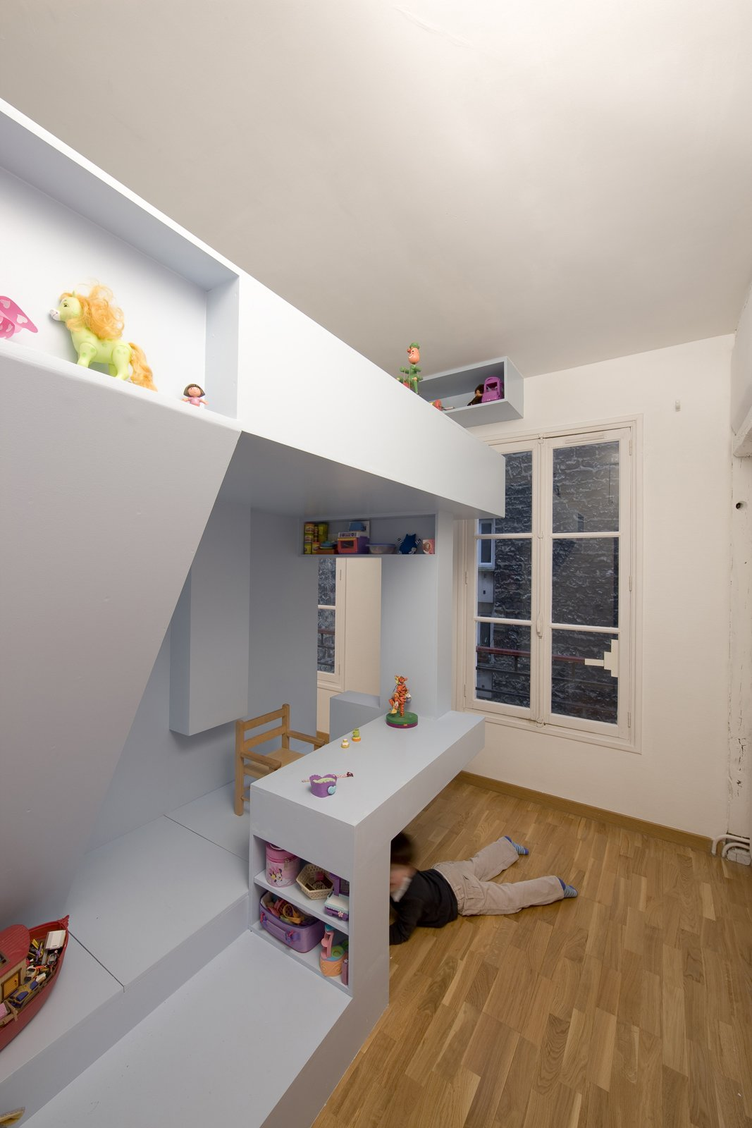 "The beauty of the design is that there's no one way to use the space; the architects let the children determine how to use the different elements of the room. Though the desk is often used for tea parties and drawing, it can also become a handy hiding place from parents or a nosy toddler brother. ""It's a house in the house,"" says Santiard. ""What's better than hiding under a table to play?""  Photo 7 of 11 in Kids' Room Renovation"