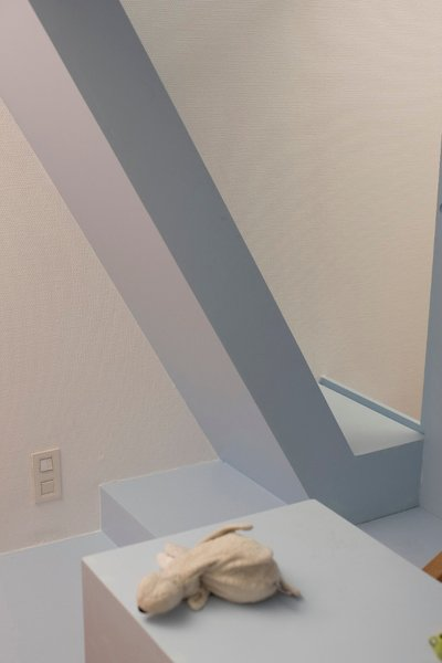 Overlapping volumes provide visual interest and make the space seem dynamic, as can be seen in this view of the steps, base, sliding door, and desk. Julo, Eva's flying guardian angel dog sits on the desk.