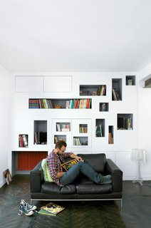Mathieu Vinciguerra reads in front of his apartment's signature storyboard shelves.