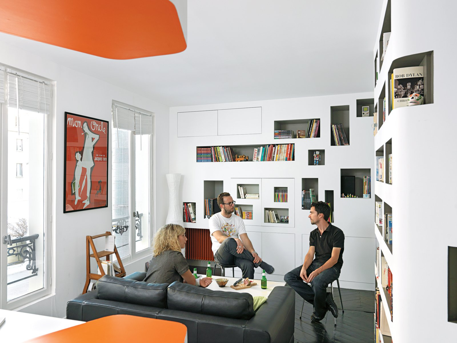 The living room is cozy, but large enough to seat a few friends. Tagged: Living Room, Bookcase, Sofa, Dark Hardwood Floor, and Coffee Tables.  Storage by Dwell from Shelf Life