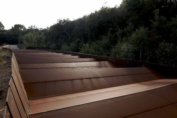 The roofline of the winery structure is defined by a sequence of parallel steel blades.