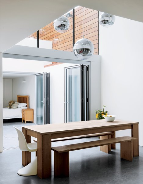 With the sliding doors open, the kitchen connects to a courtyard and spare bedroom, where friends who come over for dinner sometimes take up residence for days.