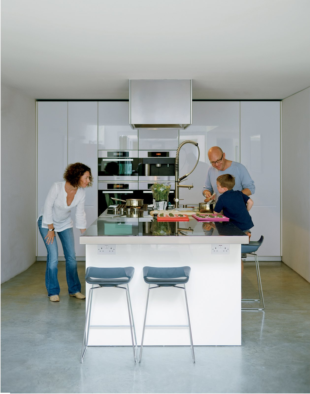 Bruce and Kirsty loved the idea of a kitchen island rather than traditional work surfaces around the walls. Bruce fancies himself a chef and hates to have his back to everyone when he's cooking. This island, from the Boffi LT line designed by Piero Lissoni, allows guests to gather around for impromptu sushi rolling or casual breakfasts. Tagged: Kitchen, Wall Oven, and White Cabinet.  Photo 5 of 10 in Composite Index