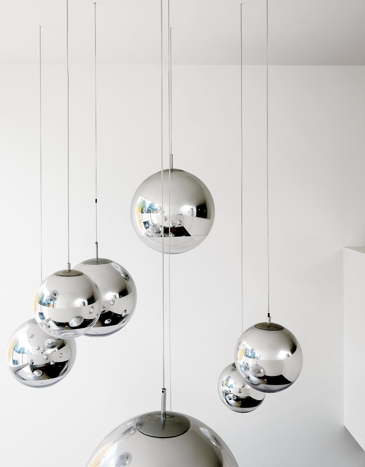"""Bruce worried about what to put in the double-height space above the kitchen table—–until he found these Tom Dixon–designed mirror balls. """"They were installed at random and when William came over that evening, he said, 'Fantastic, well done.' So we left them like that.""""  Photo 14 of 19 in How to Take a Dwell Photo from Composite Index"""