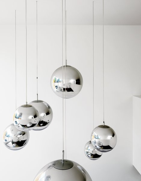 "Bruce worried about what to put in the double-height space above the kitchen table—–until he found these Tom Dixon–designed mirror balls. ""They were installed at random and when William came over that evening, he said, 'Fantastic, well done.' So we left them like that."""