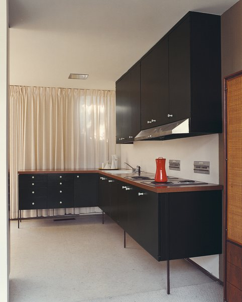 Unsightly service elements of the kitchen are tucked into the central core of the home, while a furniture-like L is situated in the rear corner and visible from the living area. Stevens had the 42 George Nelson cabinet pulls made with a CNC-router system based on an original.
