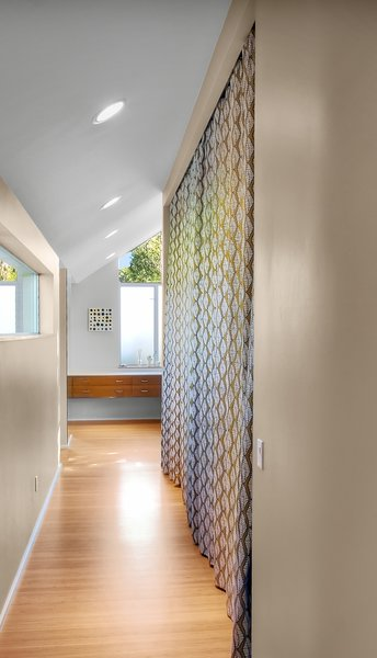 The master suite is connected to the original house by a long hallway, pictured here, which hides a closet behind the colorful curtains.