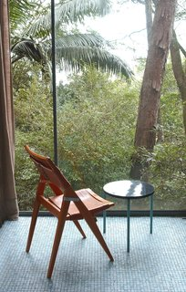 Lina Bo Bardi - Photo 10 of 14 - Her folding side chair, against the floor-to-ceiling window wall of the Glass House. Photo courtesy Espasso.