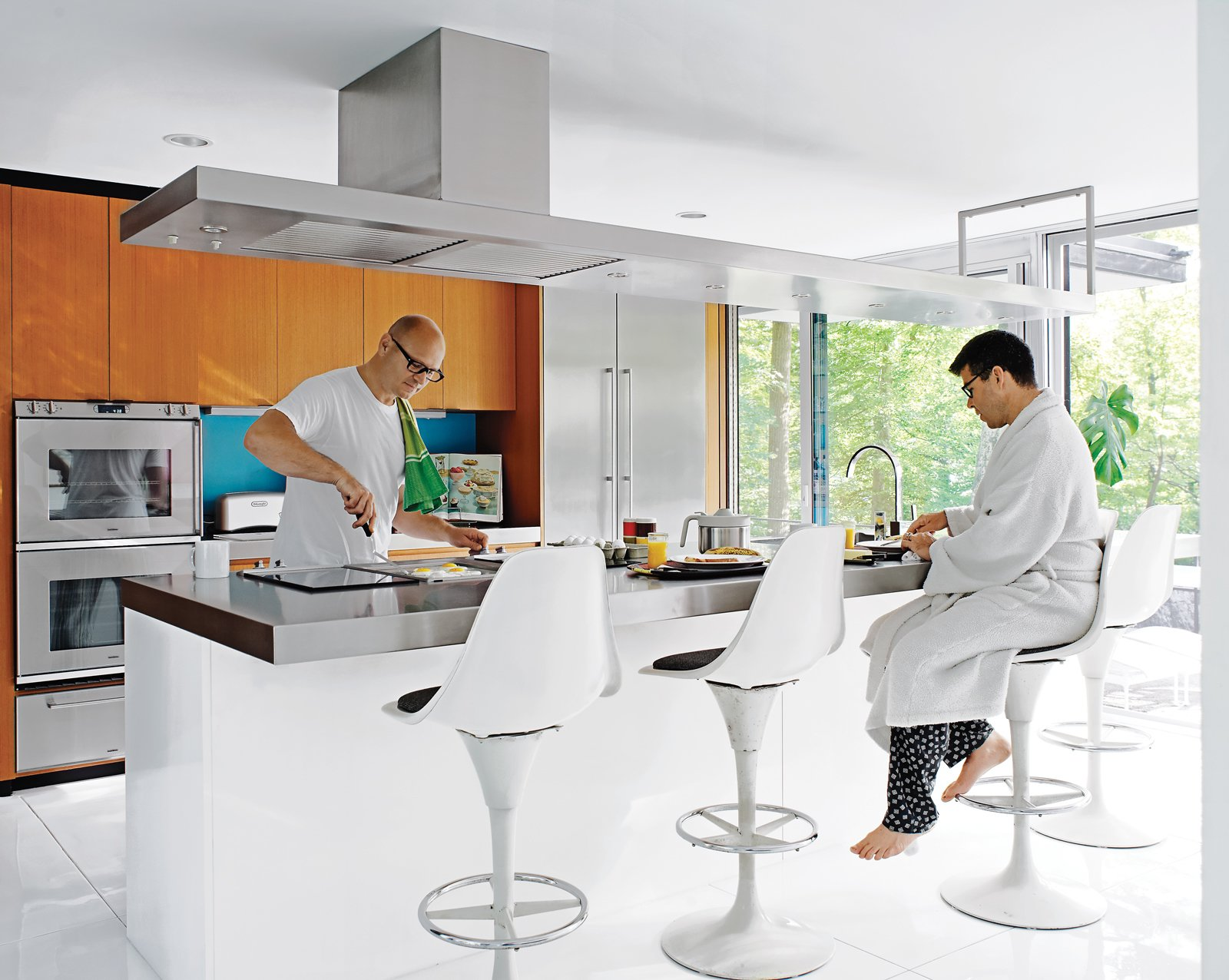 Despite their fidelity to the original structure, the residents made small changes, notably in the kitchen: The wood-veneered island was moved to create more circulation space behind it and finished in white lacquer and stainless steel. Wood cabinetry above the island was exchanged for a steel ventilation unit. Tagged: Kitchen, Metal Counter, Wall Oven, Range Hood, Refrigerator, and Wood Cabinet.  Photo 11 of 17 in Mod Men
