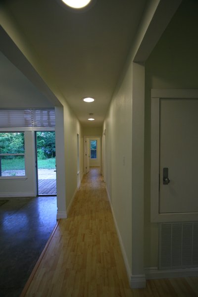 Inside the front door, a long hallway separates the public space, on the left, from the private space, which extends farther back on the right side of the home. Photo courtesy of Jared Boudreaux and Tim Hayes.