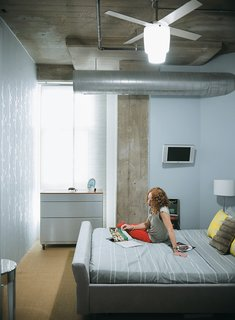 "12 ""Pro-Tips"" For Installing Wallpaper in Your Home - Photo 7 of 13 - In the adjacent bedroom, decorative touches like the silver wallpaper and mirrored regency-style side table juxtapose with the exposed concrete and duct work."